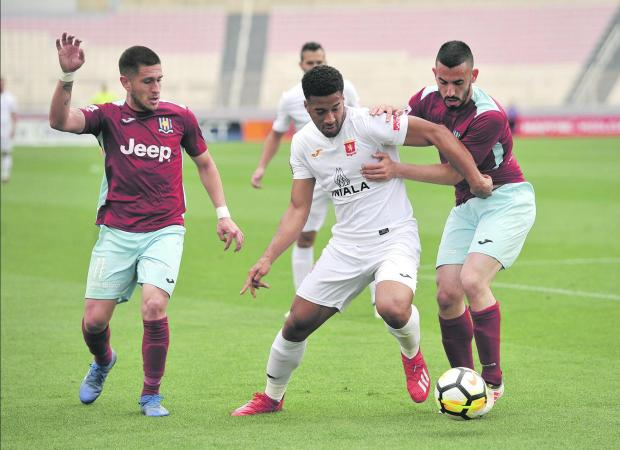 Valletta's Kyrian Nwoko (centre) moves past Sasha Borg (right) and Juan Corbalan of Gżira United.