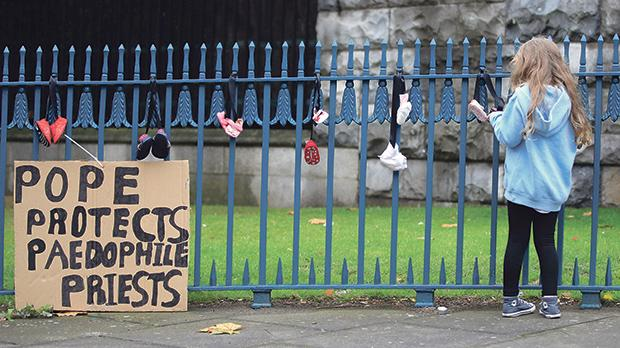 A girl ties baby shoes to a fence as part of a protest to highlight child abuse at the hands of the Catholic Church, during the visit of Pope Francis to Dublin, Ireland. Photo: Gonzalo Fuentes/Reuters