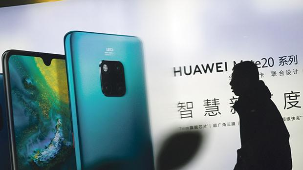 """A man walks past Huawei advertising outside a store in Beijing. """"Your cell phone will spy on you regardless of who wants to come after you. It is your billboard to the world."""" Photo: Wang Zhao/AFP"""