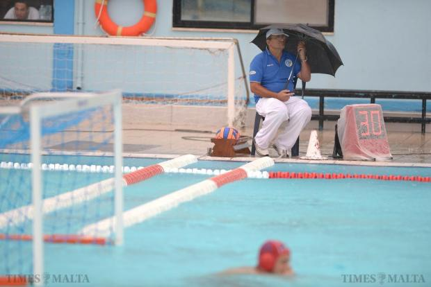 An umpire shelters under an umbrella during a waterpolo U-20 Comen Cup match between Italy and Serbia at the National Pool in Tal'Qroqq on August 16. Photo: Matthew Mirabelli