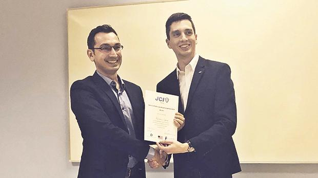 Dr Anthony Galea (left) receiving the winner's certificate from JCI Malta deputy president Christoph Schwaiger.