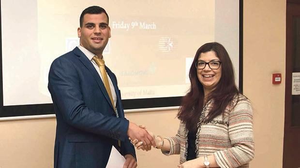 Stefan Cassar receiving the award from Prof. Lilian Azzopardi, head of the Department of Pharmacy.