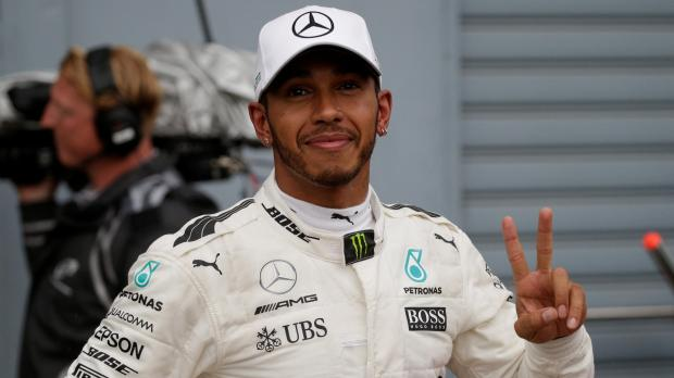 Mercedes' Lewis Hamilton celebrates after qualifying in pole position.