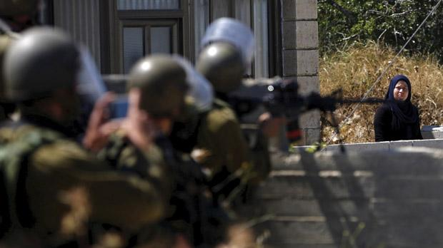 A Palestinian woman stands near Israeli soldiers during clashes in the West Bank on Friday. Photo:Reuters