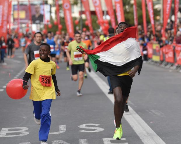 An Athlete holds a Sudanese flag at the final stage of the Malta Marathon in Sliema on February 25. An earlier version incorrectly described the flag as a Palestinian one. PHOTO: MARK ZAMMIT CORDINA