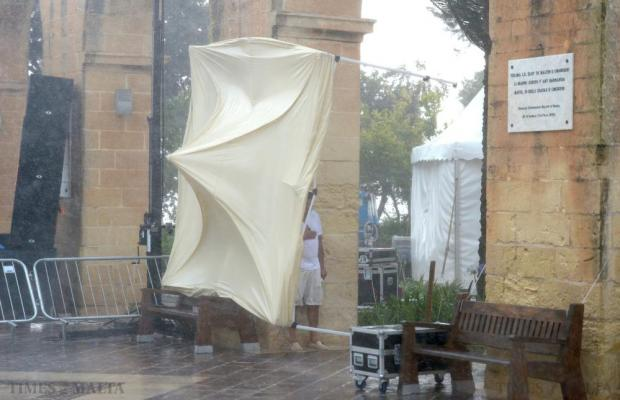 A man shelters from the rain behind a canopy which was blown over as strong winds and rain hit Barrakka Gardens during a freak storm in Valletta on August 8. Photo: Matthew Mirabelli