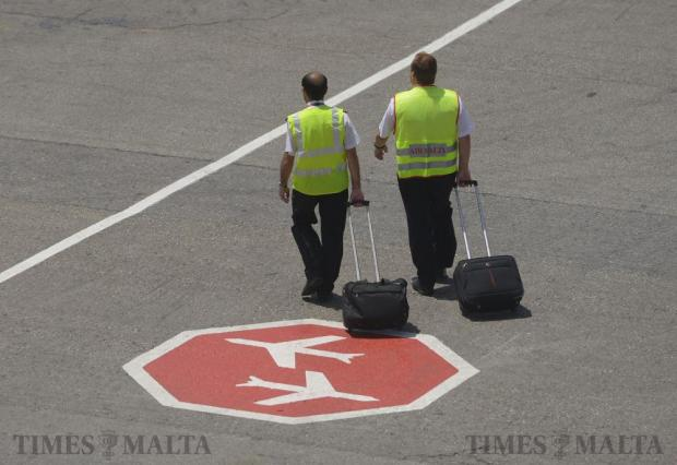 Two Air Malta pilots make there way to their aircraft on July 7, on a form of 'dress down' strike without jacket and cap, as they demand better working conditions and pay. Photo: Matthew Mirabelli