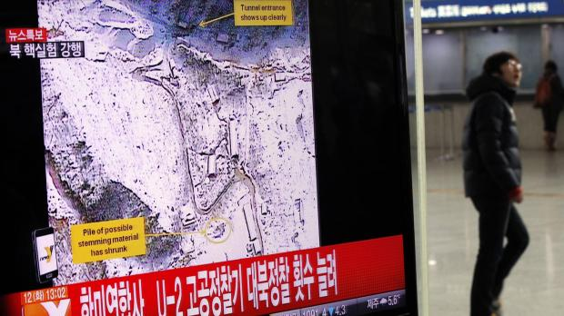 A passenger walks past a television report on North Korea's nuclear test at a railway station in Seoul.