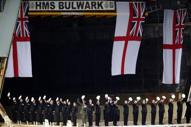 British Royal Navy officers on a floating dock beneath HMS Bulwark salute as a boat carrying Britain's Queen Elizabeth passes in Valletta's Grand Harbour during the Commonwealth Heads of Government Meeting (CHOGM) on November 28. Photo: Darrin Zammit Lupi