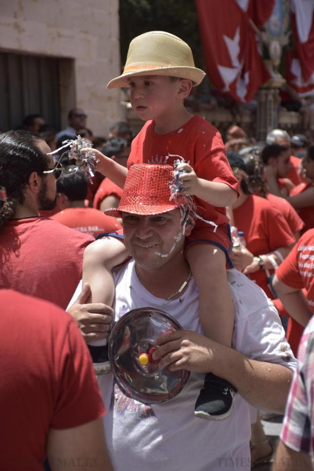 A young boy is carried on a man's shoulders during the feast of St Paul in Rabat on July 3. Photo: Mark Zammit Cordina