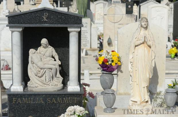 Flowers lay next to tomb stones in Mosta cemetery as mourners visit the graves of their dead relatives and friends on November 1, the eve of All Souls' Day. The day is celebrated by the Catholic Church to honour the dead. It is also recognised by some other Christian denominations. Photo: Matthew Mirabelli