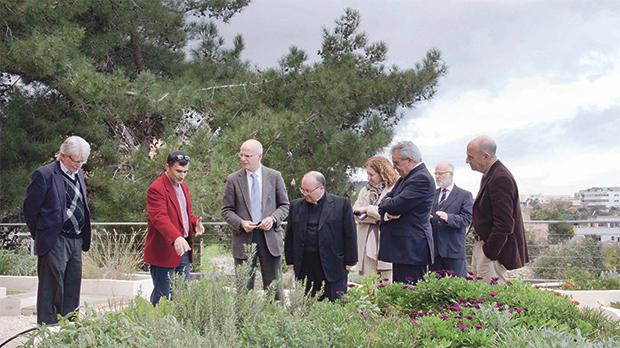 Project manager Antoine Gatt (second from left) showing Archbishop Charles Scicluna (centre) the plants forming part of the faculty's green roof.