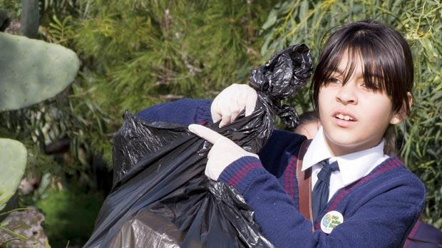 A Mellieħa Primary pupil handling a bag of rubbish.