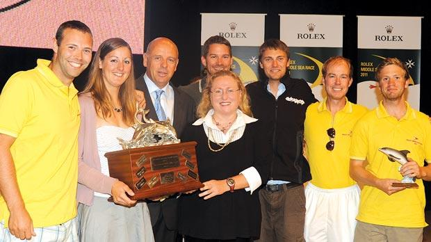 Relentless's crew holding the cetacean award trophy. Adriana Vella (centre front) presented the Bicref award. George Bonello DuPuis of the Rolex Middle Sea Race is seen on Dr Vella's right.
