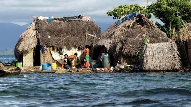 Indigenous Guna residents stand outside a house in Carti Sugdub island in Panama.