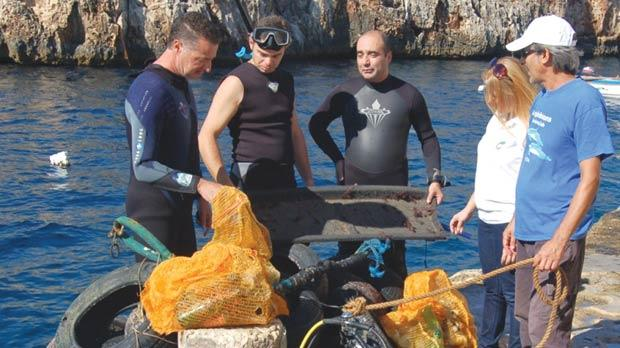 Green Pak CEO Mario Schembri (left), with Green Pak senior manager Denise Brincat (second from right), Amphibians Diving Club secretary Mark Baluci (right), and two divers looking at some of the more unusual items recovered from the seabed.