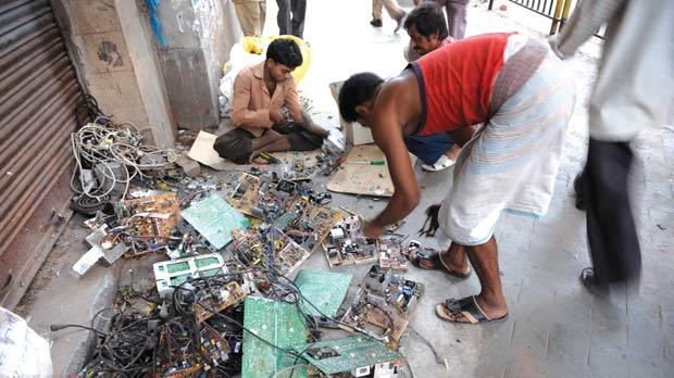 Youths dismantling reusable parts from computer waste on a pavement of Calcutta, India. Photo: AFP