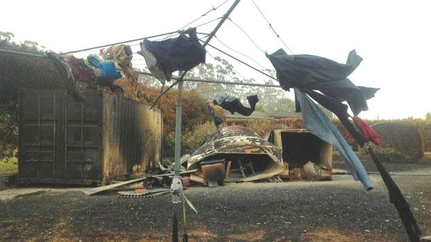 Clothes hang from a singed clothesline in a backyard affected by a bushfire at Boomer Bay, about 40km east of Hobart.