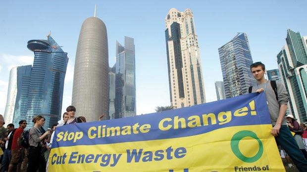 Activists standing with a banner before a march to demand action to address climate change in Doha. Photo: Reuters