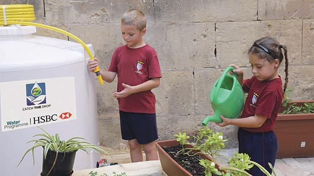 Two Senglea pupils tending to plants using water from theharvesting tanks.