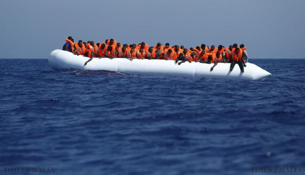 Migrants on a rubber dinghy wait to be rescued by the Migrant Offshore Aid Station (MOAS) ship MV Phoenix some 32 kilometres off the coast of Libya on August 3. 118 migrants were rescued from a rubber dinghy off Libya on Monday morning. The Phoenix, manned by personnel from international non-governmental organisations Medecins san Frontiere (MSF) and MOAS, is the first privately funded vessel to operate in the Mediterranean. Photo: Darrin Zammit Lupi