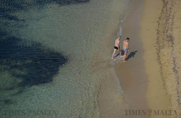 Two men enjoy the calm sea and sun at Golden Bay on November 1. Photo: Matthew Mirabelli