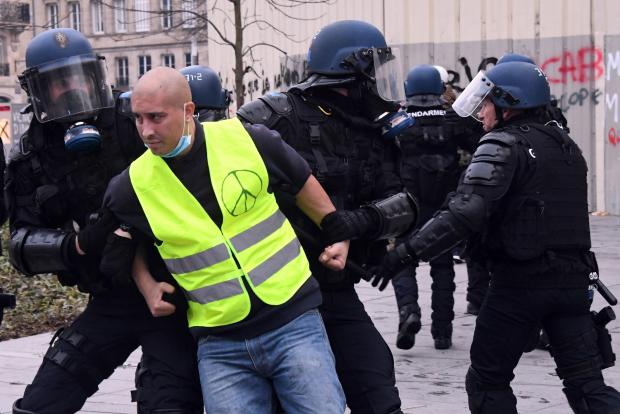 A protester is arrested by riot police. The protests are now in their 13th week. Photo: AFP