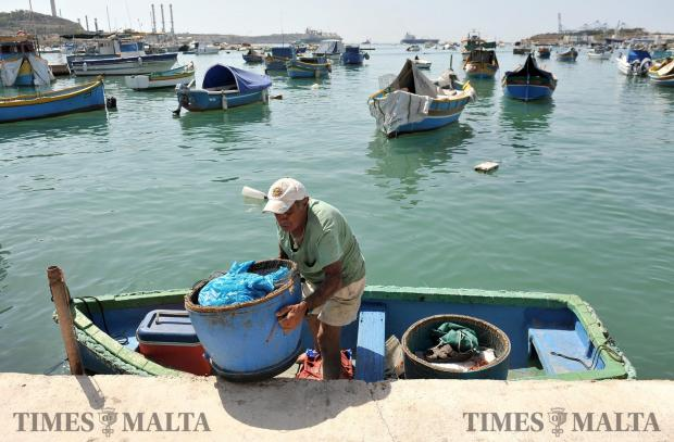 A man carries fishing nets ashore in Marsaxlokk on August 10. Photo: Chris Sant Fournier