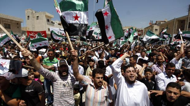 Syrians attend an anti-Bashar Assad protest after Friday prayers on the outskirts of Idlib, Syria.