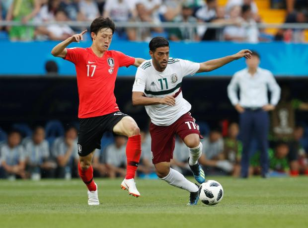 Mexico's Carlos Vela (right) charges forward against South Korea.