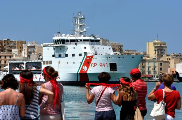 Protesters look as Italy's Diciotti coast guard vessel carrying 67 asylum seekers arrives in Trapani. Photo: AFP