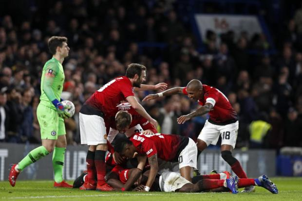 Manchester United's French midfielder Paul Pogba is congratulated by teammates after scoring their second goal.