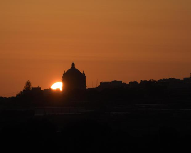 The sun sets behind the Mgarr Church on April 24. Photo: Mark Zammit Cordina