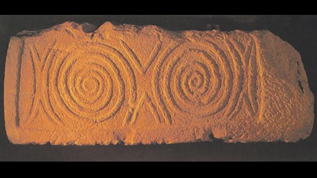 Altar slab found at Buġibba Temple, with two symmetrical spiral motifs symbolising eternity. Courtesy of Mario Mintoff of M. J. Publications Ltd