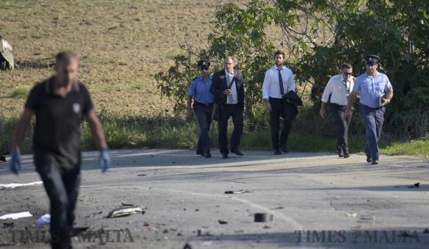 Policemen at the scene escort family members of journalist Daphne Caruana Galizia where she was brutally murdered by a car bomb in Bidnija on October 16. Photo: Mark Zammit Cordina