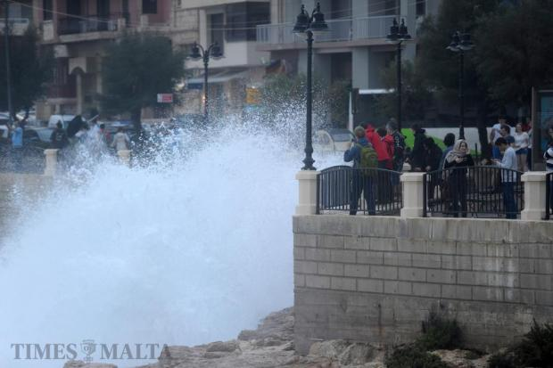 People photograph high waves on the Sliema front on October 29. Photo: Steve Zammit Lupi