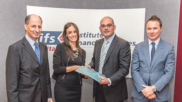 Daphne Ciantar receiving a commemorative gift from IFS Malta president Kenneth Micallef in the presence of Peter Calleya, IFS Malta vice president (left) and Rob Thompson, relationship director at the London Institute of Banking and Finance.