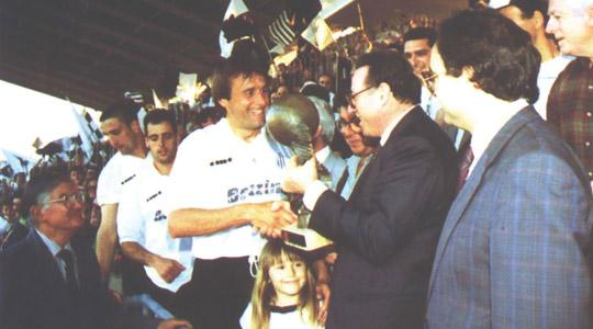 Hibs captain Michael Woods receiving the league trophy from MFA president Joe Mifsud.