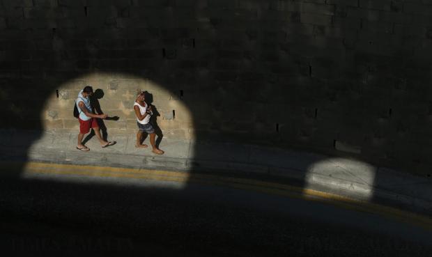 Tourists walk along a pavement in Valletta on July 25. Photo: Darrin Zammit Lupi