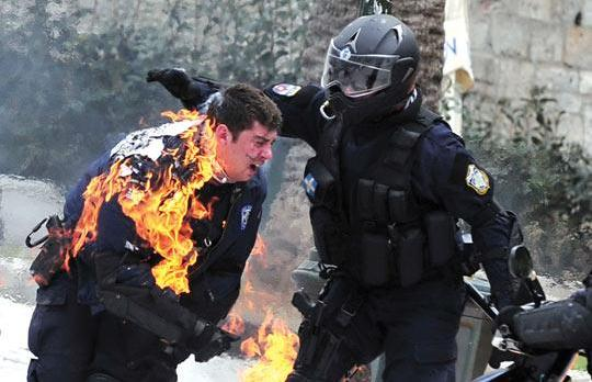 A policeman on fire is helped by a colleague as fighting broke out between protesters and police in central Athens, yesterday. Photo: Aris Messinis/AFP