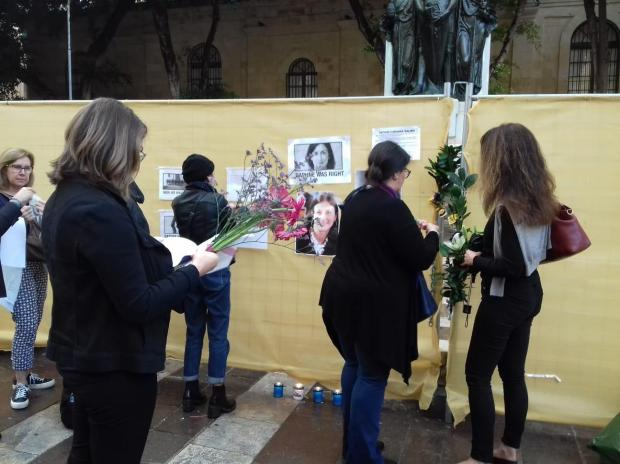 Activists placing flowers at the covered memorial on Saturday.