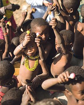 Children raise their hands in glee as they enjoy the rare treat of a sweet in Wush Wush, Ethiopia.