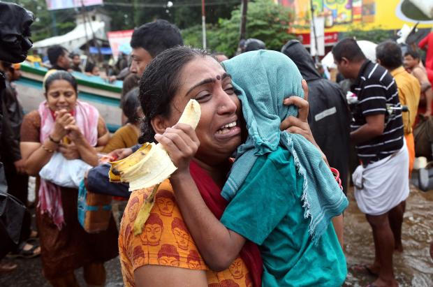 A woman cries as she holds her son after they were evacuated from a flooded area in Aluva. Photo: Reuters