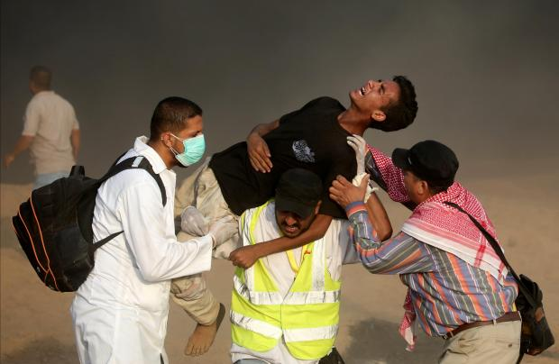 Medics carry a wounded Palestinian man during a protest, demanding Palestinians' right to return to their homeland.