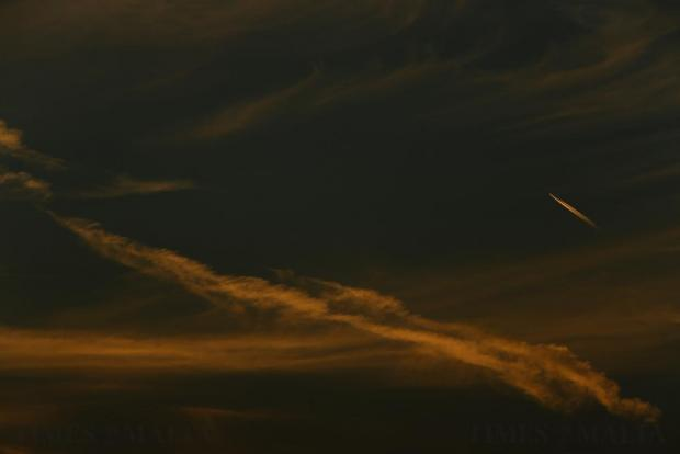 A passenger airplane leaves contrails in the sky as it flies over Malta at sunset on October 25. Photo: Darrin Zammit Lupi