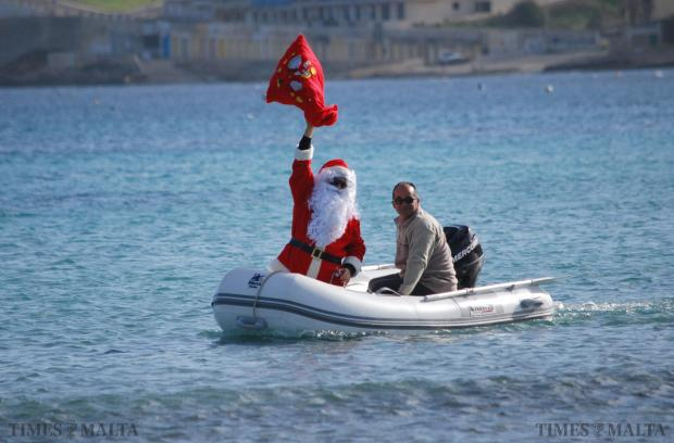 Father Christmas makes his way to shore on a dinghy at Għadira on December 16, delighting primary schoolchildren from the Mellieħa school in what is becoming a traditional event for them. Photo: Mark Zammit Cordina