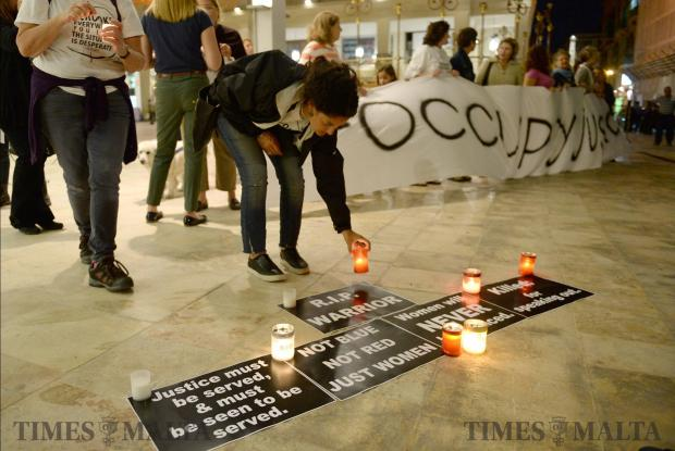 A lady lights a candle during a protest organised by Occupy Justice outside Parliament on October 30 demanding justice following the murder of Daphne Caruana Galizia. Photo: Matthew Mirabelli