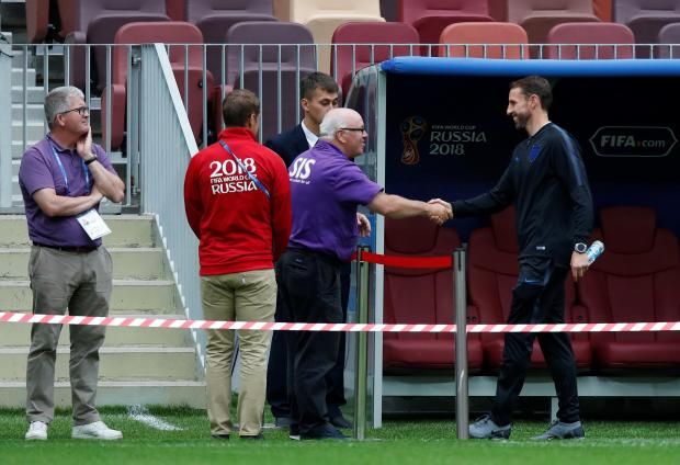 England manager Gareth Southgate shakes hands with head groundsman Alan Ferguson on the pitch.