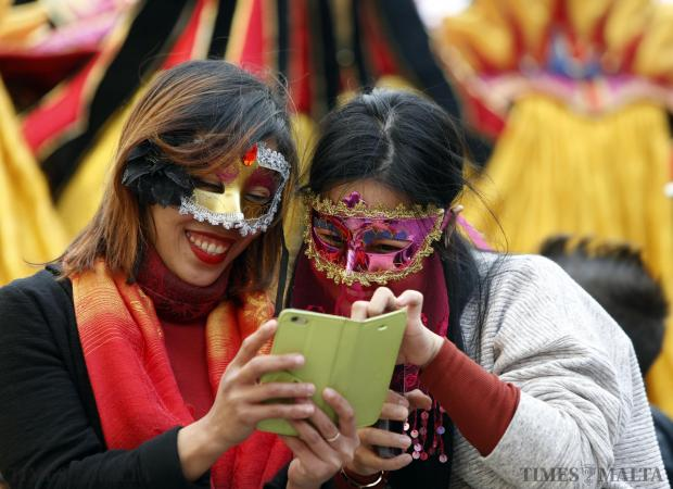 Two masked tourists look at photos on a phone during carnival festivities in Valletta on February 7. Photo: Darrin Zammit Lupi