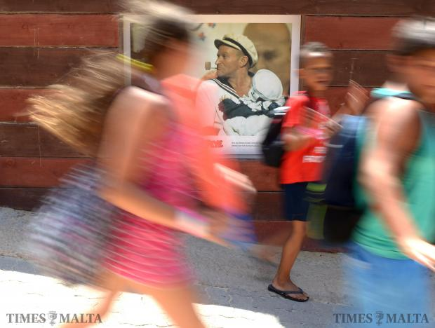 Children walk past one of the posters of Robin Williams in character at Popeye Village in Mellieha on August 12. The actor was found dead at his California home on Monday following a long period of depression. Photo: Matthew Mirabelli